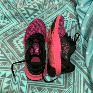 pink and black Underarmour tennis shoes